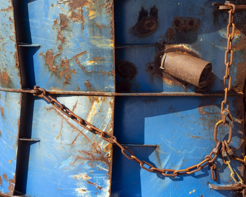 close up view of blue ship hull w/ rusted patches and chain