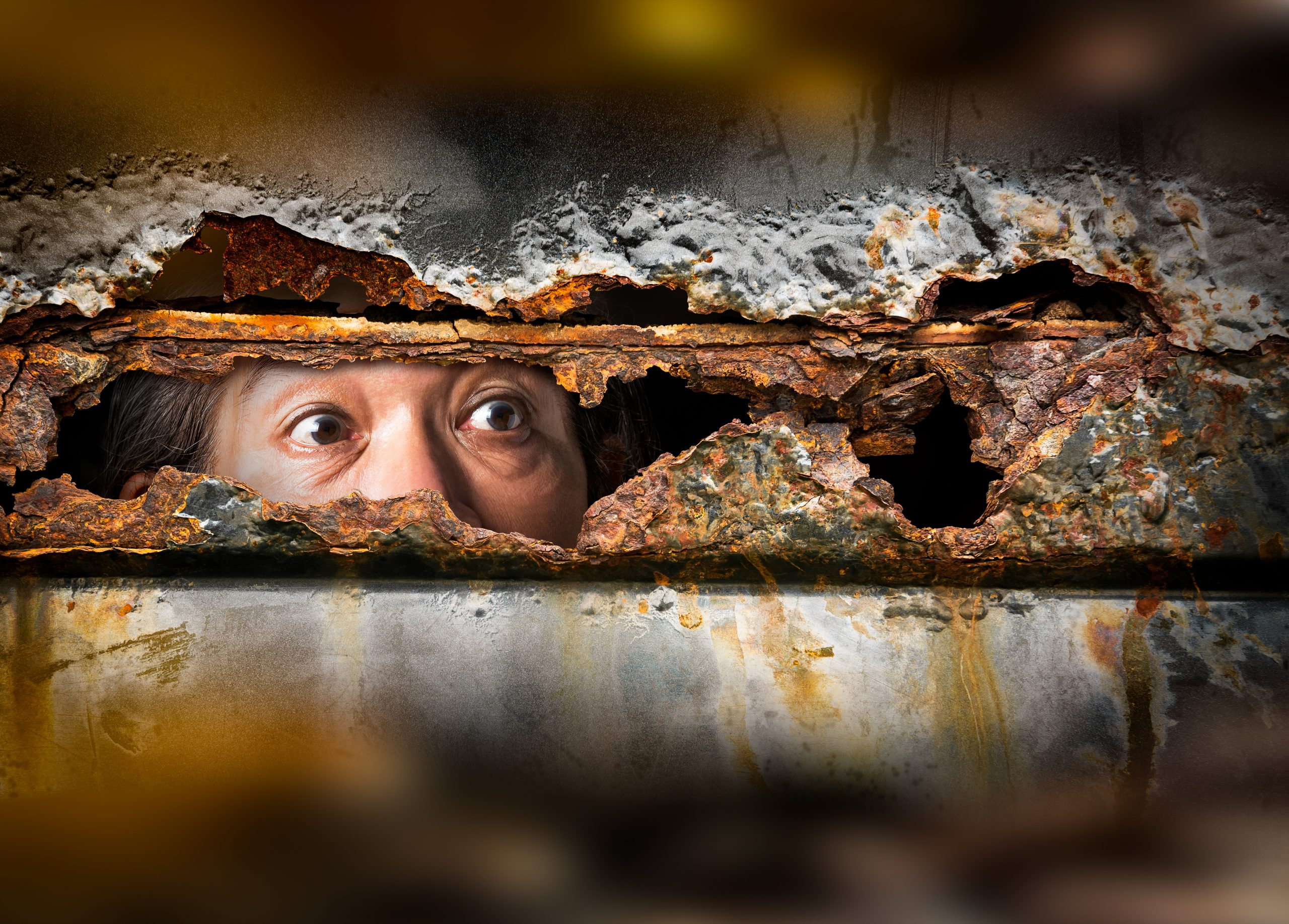A pair of eyes peering through a rusted through piece of metal