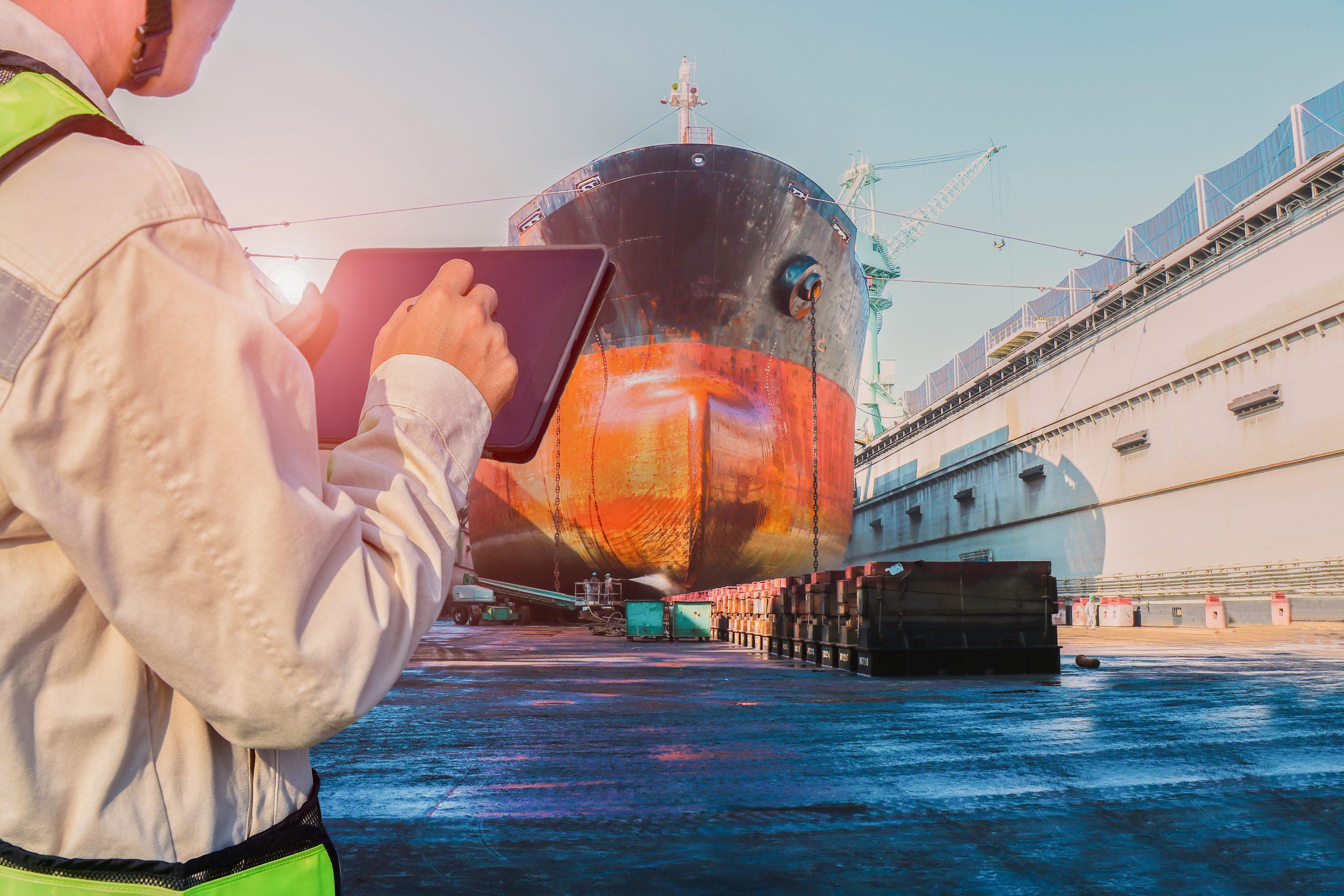 Surveyor inspecting ship in floating dock