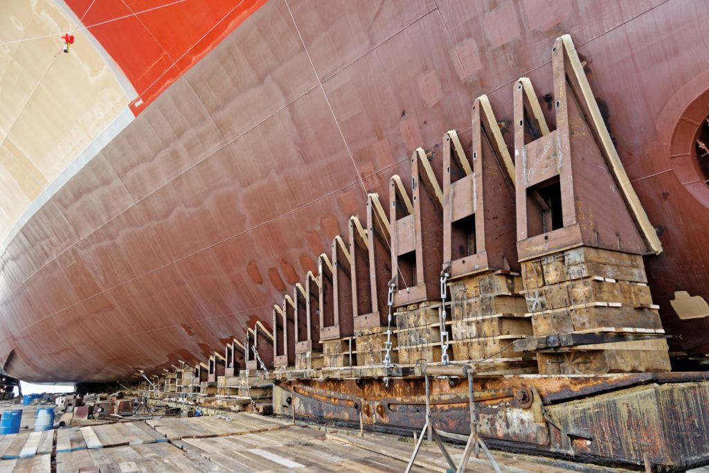 Low angle shot of a hull of ship in drydock resting on pilings ready for launch