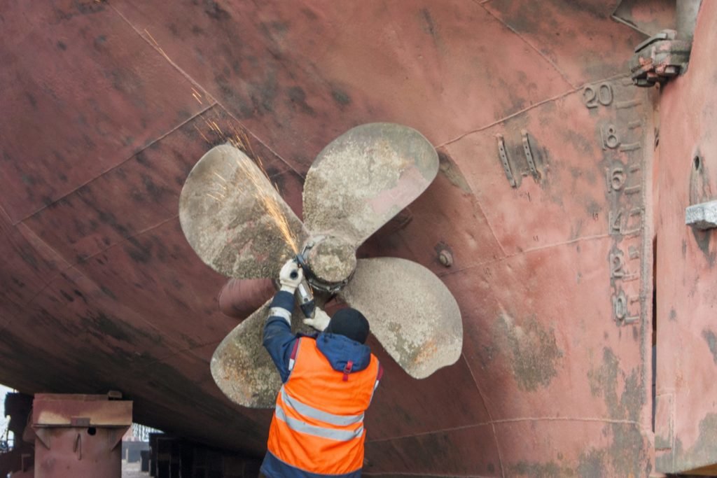Man working with a torch on a propeller of a ship in drydock