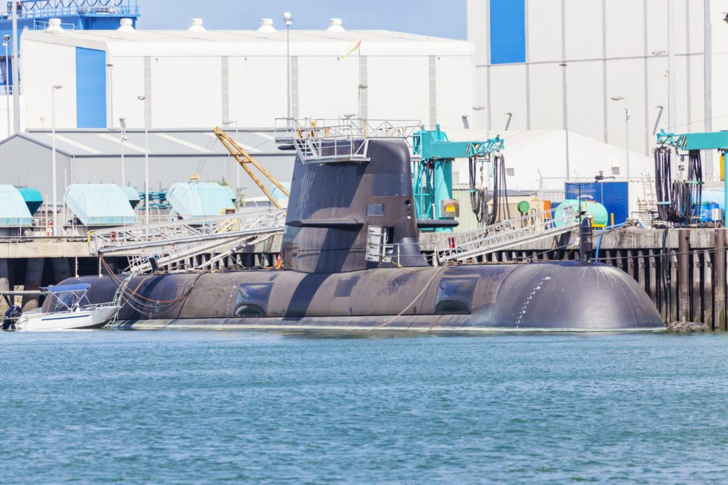 Submarine in partially submerged in water at a naval shipyard