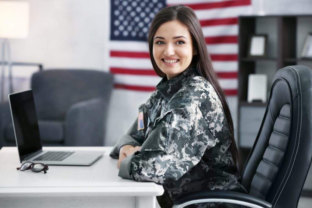 Female solder smiling at the camera, sitting at a desk with a laptop