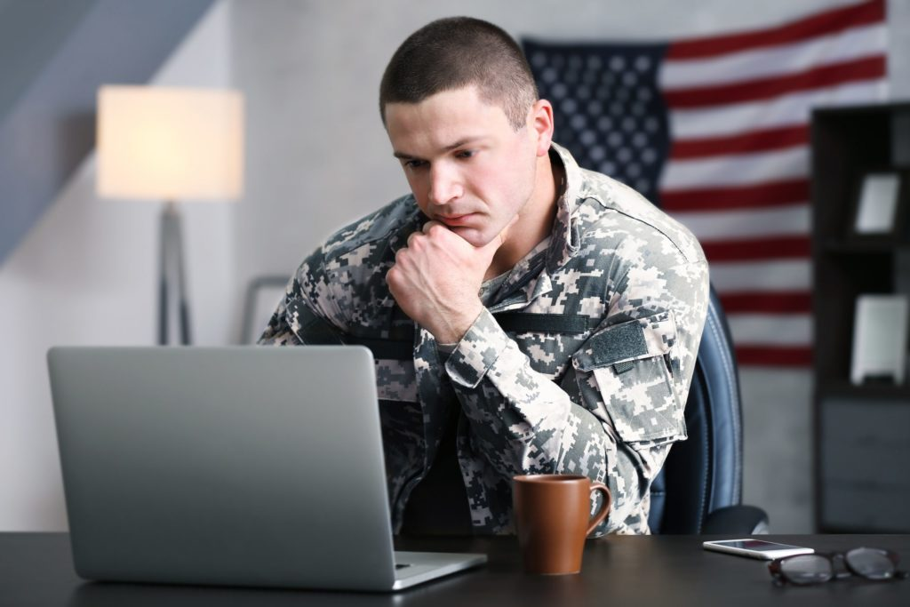Soldier sitting at desk leaning on one elbow studying a laptop screen