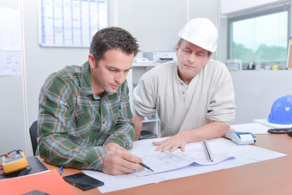 Two gentlemen, one on right wearing a hard hat, reviewing blueprints sitting at a desk