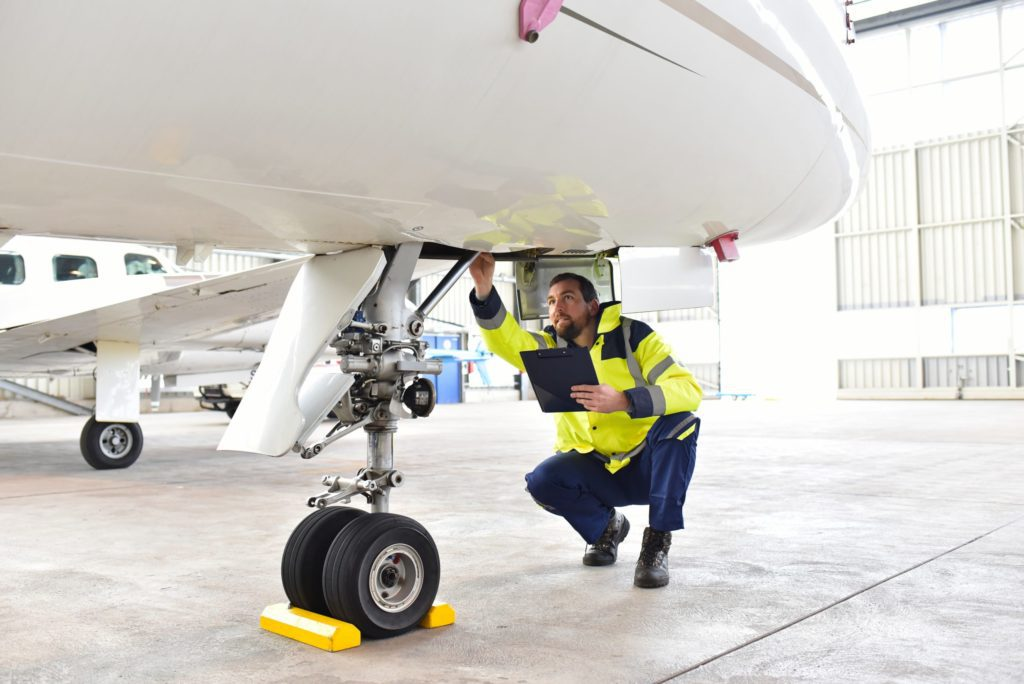 Mechanic assesses needed repairs to a plane.