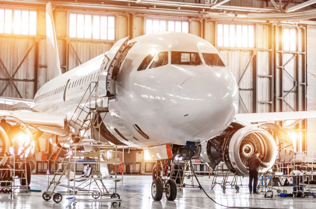 Passenger commercial airplane on maintenance of engine turbo jet and fuselage repair in airport hangar. Aircraft with open hood on the nose and engines, as well as the luggage compartment