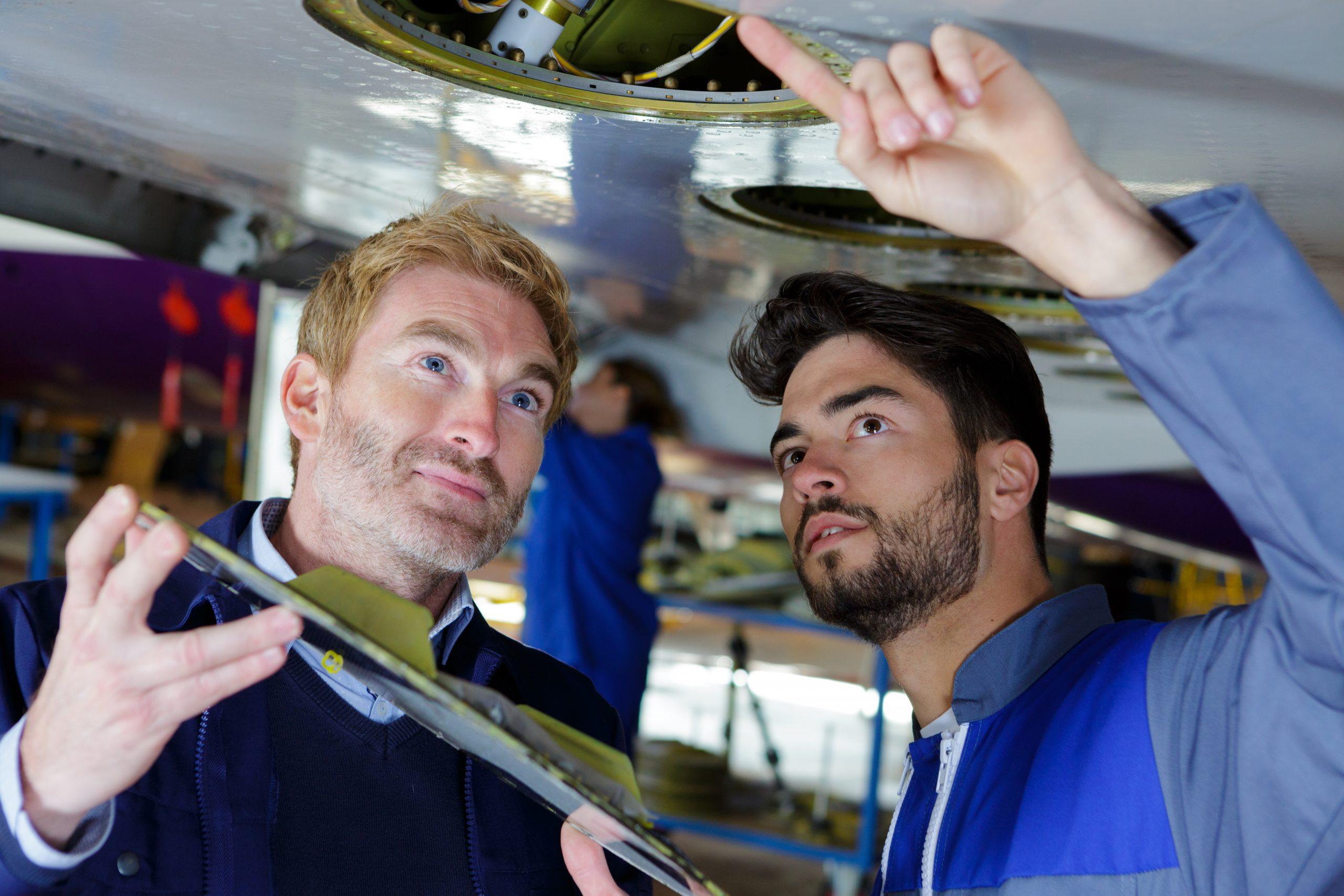 repairmen working on an airplane engine