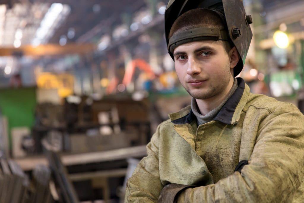 man in welding jacket with welding mask on head