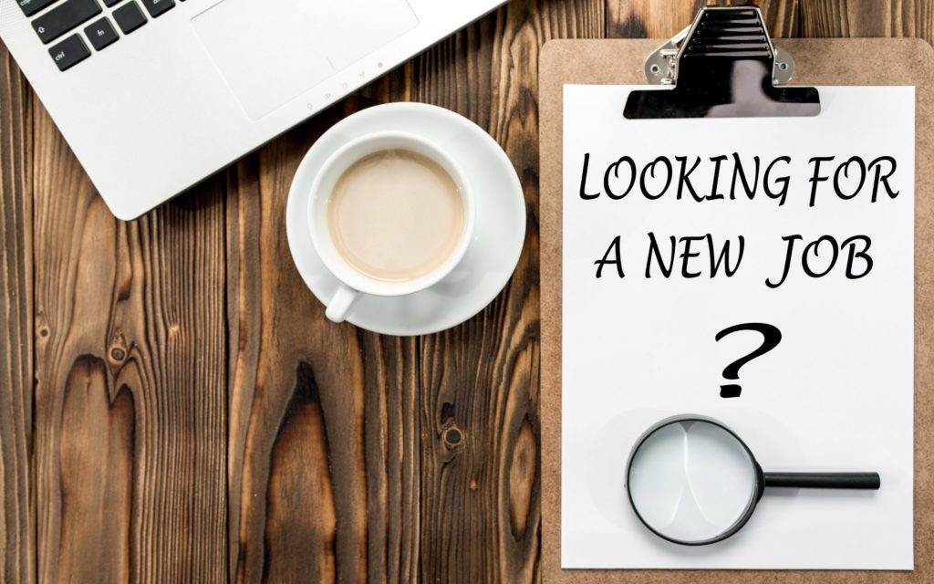 """Image with coffee cup, computer and clipboard with """"Looking for a New Job?"""" on a piece of paper"""