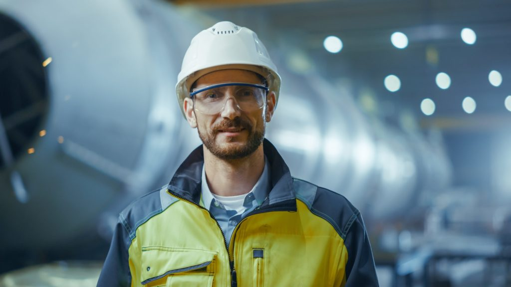 Portrait of Smiling Professional Heavy Industry Engineer / Worker Wearing Safety Uniform, Goggles and Hard Hat.