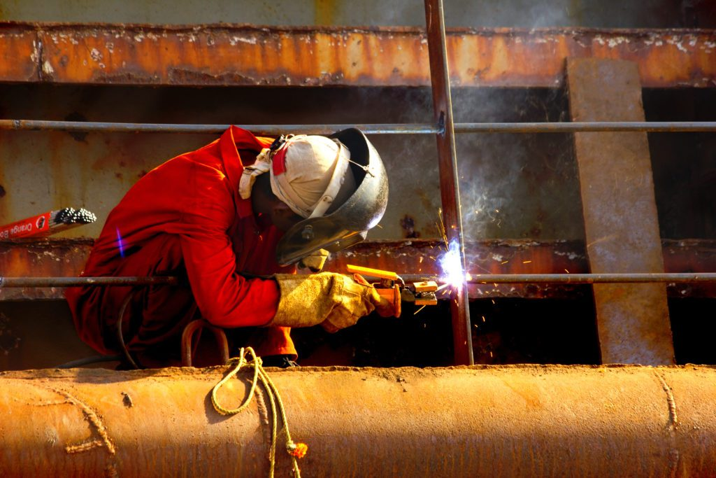 A man making ship repairs by welding.