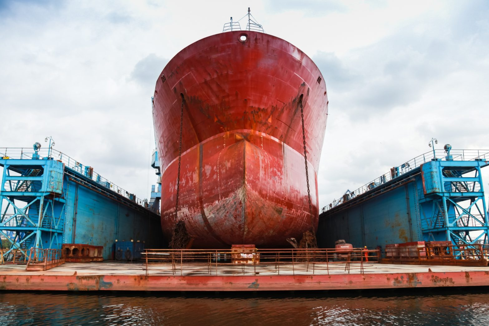 A large red tanker ship docked for repair at a shipyard.