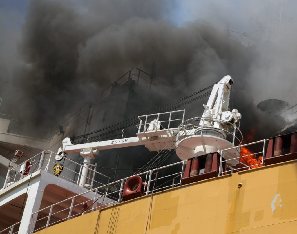Smoke hovering over a large yellow ship during a shipyard fire. Mobile cold spray repair can help reduce risk of shipyard fires.