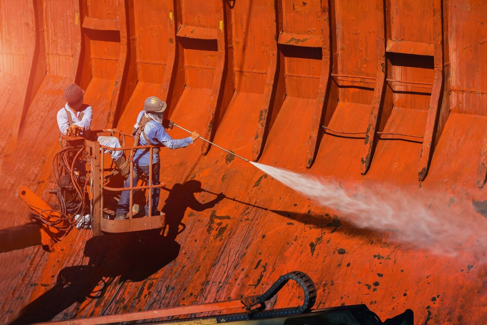 Washing and cleaning, worker High pressure water jet to cleaning with Old ship washing on Trucks have sherry piker wearing safety harness with ppe in side cargo hold under ship repair in floating dry dock in shipyard. Preparing surface for corrosion resistant coating application