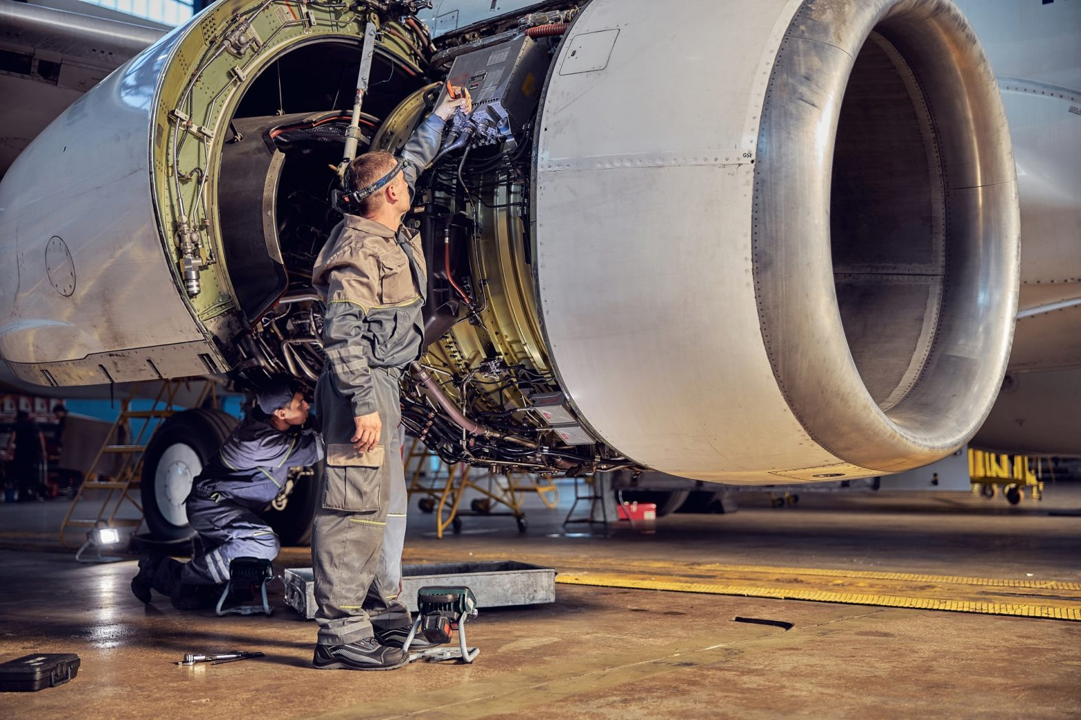 Full length portrait of 2 technicians who are repairing aircraft in the aviation hangar