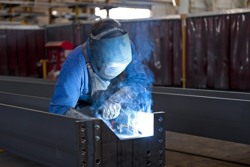 Welder works on metal fabrication, fumes billow up into his face which is protected by a mask