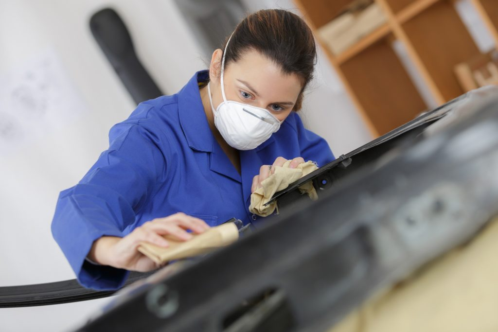 woman worker wearing mask as she preps for surface coating