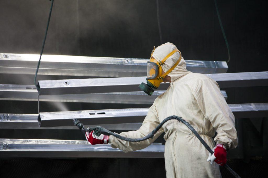 Industrial painter applying surface coating to metal